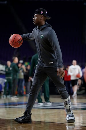 Injured Michigan State guard Joshua Langford dribbles on the court during a practice session for the semifinals of the Final Four.