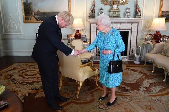 Britain's Queen Elizabeth II welcomes newly elected leader of the Conservative party Boris Johnson during an audience at Buckingham Palace, London, Wednesday July 24, 2019, where she invited him to become Prime Minister and form a new government.