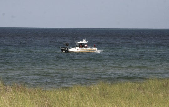 A Mason County Sheriff's Office boat searches the waters near the Lake Michigan beach house at Ludington State Park on Tuesday morning.