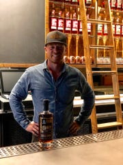 Chris Fredrickson, one of the co-founders of Traverse City Whiskey Co. stands with his award-winning Barrel Proof Bourbon.