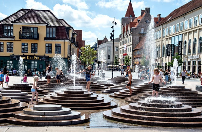 People cool down in the fountains as temperatures reached 30 degrees Celsius, at Toldbod Plads in Aalborg, Denmark, on Wednesday.