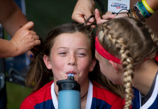 Peyton Pryor gets a double-team hair braiding by a team mom and her sister before the Midwest Astros South '07 softball team's first pool game at the Newburgh Softball Fields Wednesday afternoon, July 17, 2019.