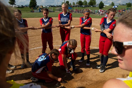 "The Midwest Astros South '07 gather in the pitching circle to honor local softball player Kate Bruggenschmidt – who was killed in an ATV accident in 2015 – by writing ""Play 4 Kate"" on the pitching rubber and reciting ""The Lord's Prayer"" with the Indiana Ducks after their pool game Wednesday afternoon, July 17, 2019. The Astros perform this ritual after every game and also gather together before each inning to shout ""Play for Kate."""
