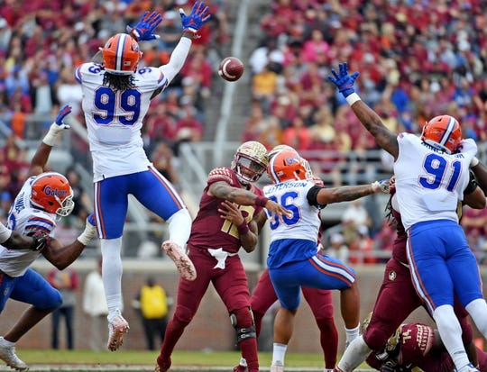Nov 24, 2018; Tallahassee, FL, USA; Florida Gators defensive linemen Jachai Polite (99) and Marlon Dunlap Jr. (91) try to block a pass from Florida State Seminoles quarterback Deondre Francois (12) during the second half at Doak Campbell Stadium. Mandatory Credit: Melina Myers-USA TODAY Sports