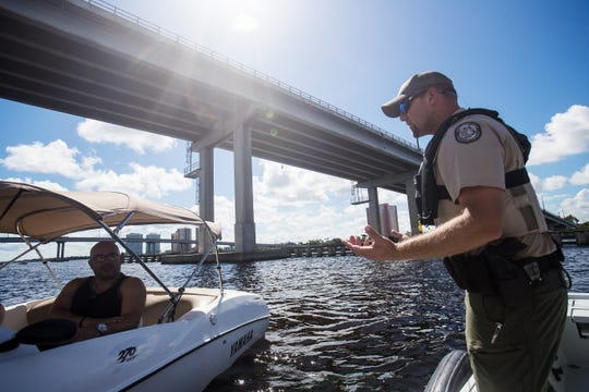 Brian Norris, an officer and spokesperson for the Florida Fish and Wildlife Conservation Commission discusses manatee zones with boaters Fred Dickens and Juan Colon in the Caloosahatchee River on Wednesday July, 24, 2019. Lee County manatee deaths are trending higher than normal with 22 boat related deaths so far this year. FWC is asking boaters to be aware of manatee zones and areas where manatees feed.