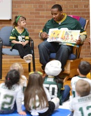 Green Bay Packers defensive end Mike Daniels reads to 4-year-old kindergarten students in 2013 at Beaumont Elementary School.