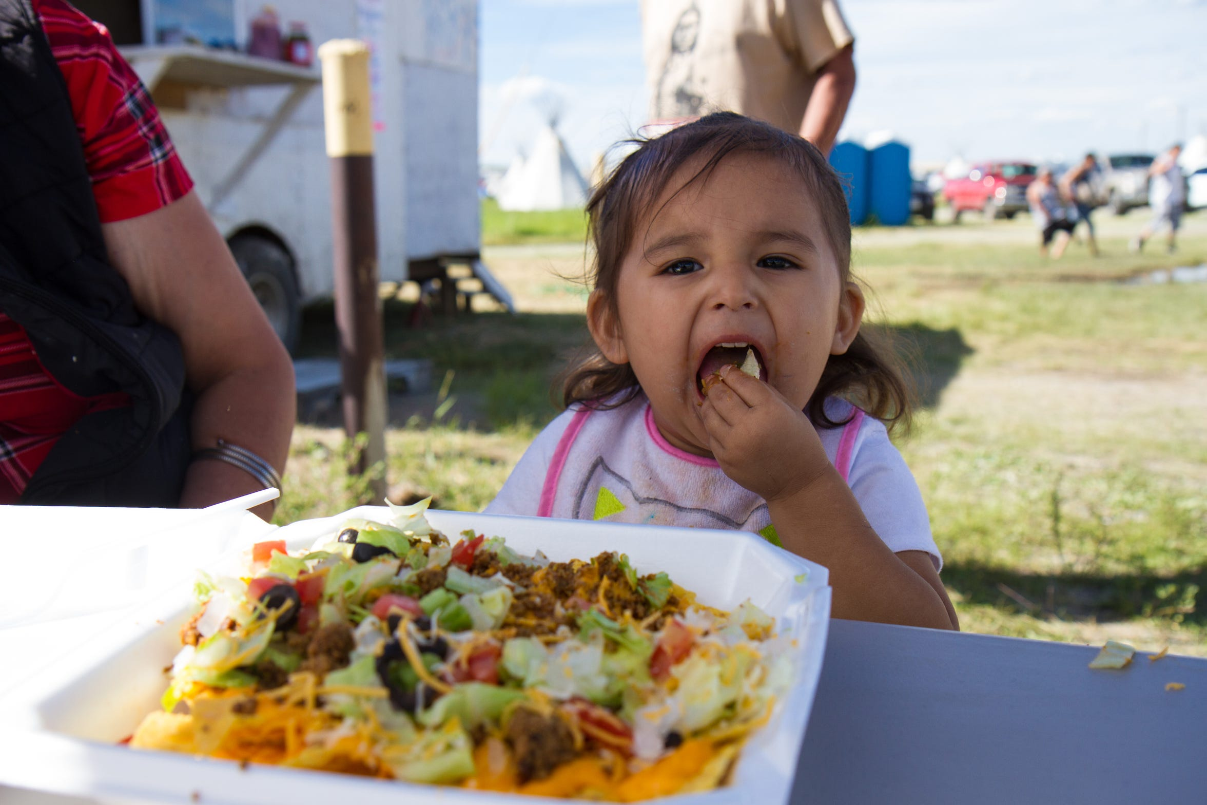 Uriel's little sister, Brielle Tatsey enjoying some Flippin' Mad Taco nachos at the 68th annual North American Indian Days