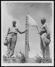"Adm. Chester W. Nimitz and Guam Island Commander Marine Maj. Gen. H.L. Larsen stand by a Japanese monument on Mount Alutom on 11 August 1944. The Japanese inscription is ""The Day of Bestowal by Imperial Edict, July 1942."""