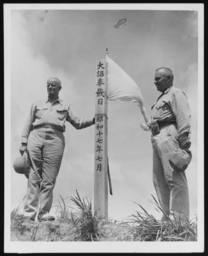 """Adm. Chester W. Nimitz and Guam Island Commander Marine Maj. Gen. H.L. Larsen stand by a Japanese monument on Mount Alutom on 11 August 1944. The Japanese inscription is """"The Day of Bestowal by Imperial Edict, July 1942."""""""