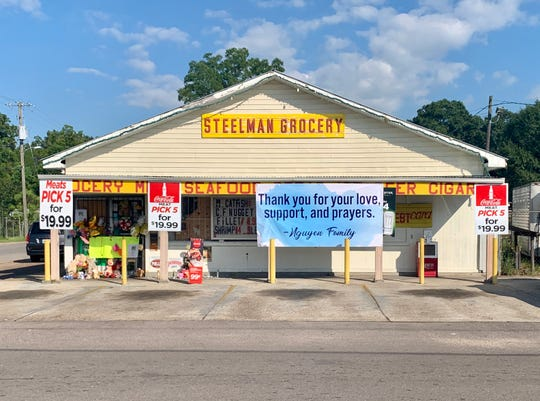 The Nguyen family hangs a sign outside their Steelman Grocery store on Wednesday, July 24, 2019. The community has come out to show support for the family after 59-year-old Lisa Nguyen was shot and killed during an armed robbery there on Saturday, July 20, 2019.
