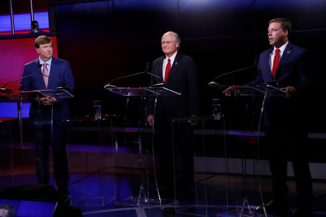 Lt. Gov. Tate Reeves, left, and former state Supreme Court Chief Justice Bill Waller Jr., center, listen to Rep. Robert Foster, R-Hernando, answer a question during a GOP gubernatorial primary debate in Jackson, Miss., Tuesday, July 23, 2019.