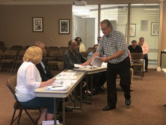 Brent Lay, a former private school administrator in Middle Tennessee, passes out his 24-page proposal to the JMCSS long-range planning committee Tuesday.