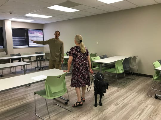 Basil Farris with the disAbility Resource Center talks to interim director Katherine Moore, with her service dog, Duke, about placement of tables for wheelchair users in the new event room. The DRC will have an open house 1-4 p.m. Friday.