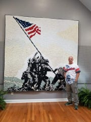 Veteran Andrew Lee stands next to his quilt depicting the raising of the flag at Iwo Jima.