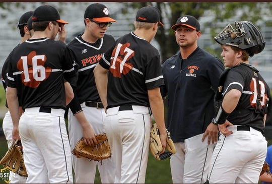Coach Logan Dalton leads a meeting of the minds on the mound during the 2019 season at Powell High.