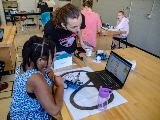 Instructor Nicholas Babineaux helps Damanii Daigre with her coding for her robot. Wednesday, July 24, 2019