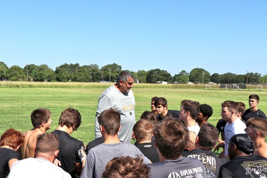 Kaplan football coach Tank Lotief instructs his team at practice.