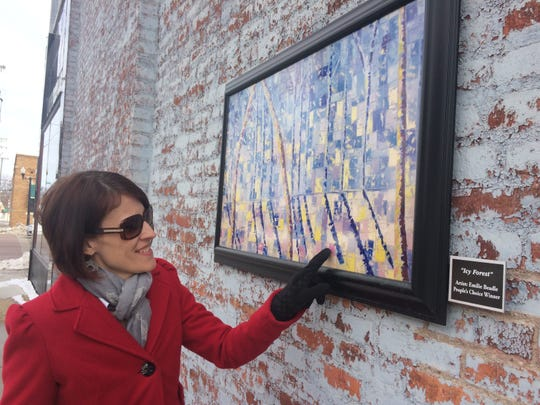 "Cathleen Edgerly looks at a copy of the ""Icy Forest"" painting that hung on the outer wall of the Howell Opera House in this 2016 photo."