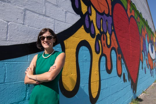 Cathleen Edgerly, director of the Howell Downtown Development Authority and chief operating officer of Howell Main Street Inc., poses next to one of the murals installed throughout downtown Howell Wednesday, July 24, 2019 thanks to efforts by her department. Edgerly will be leaving her position to take a new job in Lansing.