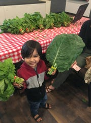 A child holds fresh greens from a Fresh Stop Market.