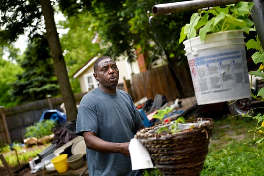 Clarence Walker talks about gardening in his backyard near hanging cucumber and strawberry plants at his home on Thursday, July 18, 2019, in Lansing.