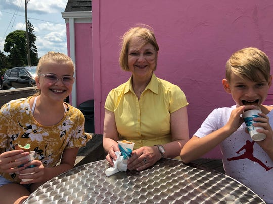 Ava Sonnemann, 12, grandma and Brady Sonnemann, 10, enjoy conuts on the deck outside of Scream 'N Conuts.