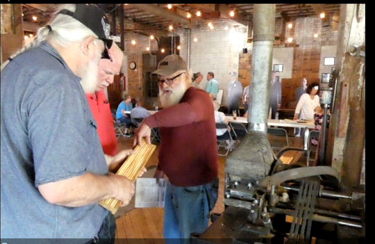 "Wayne Clark, left, and Earl Sayre, at right, volunteers at the Shawshank Woodshop and Museum, show a visitor the grooves in the wood made by the shaper machine in the woodshop in Upper Sandusky where scenes from ""The Shawshank Redemption"" were filmed in 1993."
