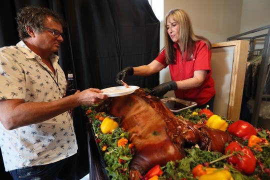 Melissa Cookston serves up her whole hog bbq at Let It Fly sports bar, a business venture of Memphis Basketball assistant coach Mike Miller, during a preview event at the Germantown location on Tuesday, July 23, 2019. The official public opening of the bar is scheduled for late August.
