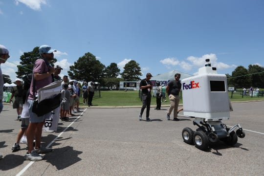 FedEx's automatronic robot Roxo drives past fans at the WGC-FedEx St. Jude Invitational at TPC Southwind on Wednesday, July 24, 2019.