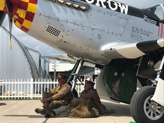 World War II re-enactors Kevin Wisniewski of Milwaukee (left) and Steve Zahareas of Schaumburg, Ill. find shade underneath a P-51 Mustang painted in the color scheme of World War II triple ace Bud Anderson as they listen to Anderson speak during EAA AirVenture in Oshkosh.