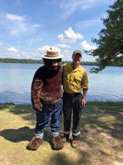 Smokey Bear stands with a forester in front of a Wisconsin lake.
