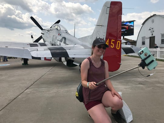 Kelly Doherty of Wichita, Kansas, takes a selfie next to her favorite plane, the P-51 Mustang, at EAA AirVenture in Oshkosh. Doherty came to the show to hear World War II triple ace Bud Anderson, 97, speak about his experiences flying the Mustang.
