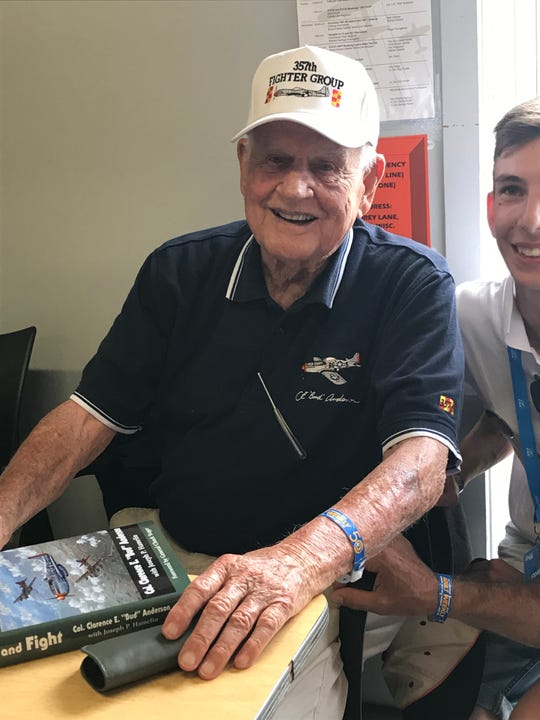 "Clarence ""Bud"" Anderson, 97, signs copies of his book at EAA AirVenture in Oshkosh. Anderson was a triple ace during World War II in P-51 Mustangs."