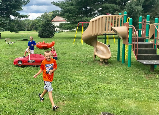 Carter Grooms (orange shirt), Seth Linton (blue) and Lia Linton (pink) play at the recently-improved Coble Park on Ohio Street in Little Texas.