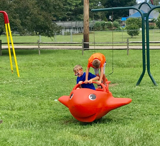Seth Linton (blue shirt) and Carter Grooms play on new equipment at Coble Park on Ohio Street in Little Texas.