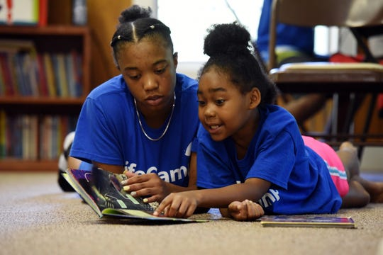 Three hundred kids daily, ages 5 to 13, take a 50-minute bus ride from Newark to LifeCamp in Pottersville, NJ. Sahara Lewis, 8, reads a book with her counselor Dynajah Speight of Linden.