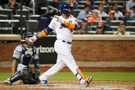 New York Mets' Robinson Cano watches his solo home run during the fourth inning of a baseball game against the San Diego Padres, Tuesday, July 23, 2019, in New York. San Diego Padres catcher Francisco Mejia is behind the plate. (AP Photo/Kathy Willens)