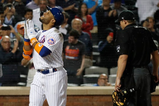 New York Mets' Robinson Cano, left, reacts crossing the plate after hitting the third of three home runs in a baseball game against the San Diego Padres, Tuesday, July 23, 2019, in New York. The third home run, a two-run blast, came in the seventh inning of Padres reliever Logan Allen. Home plate umpire Tripp Gibson is at right. (AP Photo/Kathy Willens)