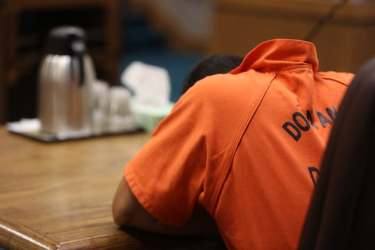 Texas man Angel G. Martinez, 23, puts his head down during his pre-trial detention hearing in Third Judicial District Court in Las Cruces, Wednesday July 24, 2019.