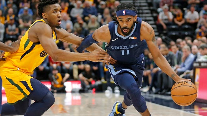 Memphis Grizzlies guard Mike Conley (11) drives around Utah Jazz guard Donovan Mitchell, left, in the first half of an NBA basketball game Monday, Oct. 22, 2018, in Salt Lake City. (Rick Bowmer | AP file photo)