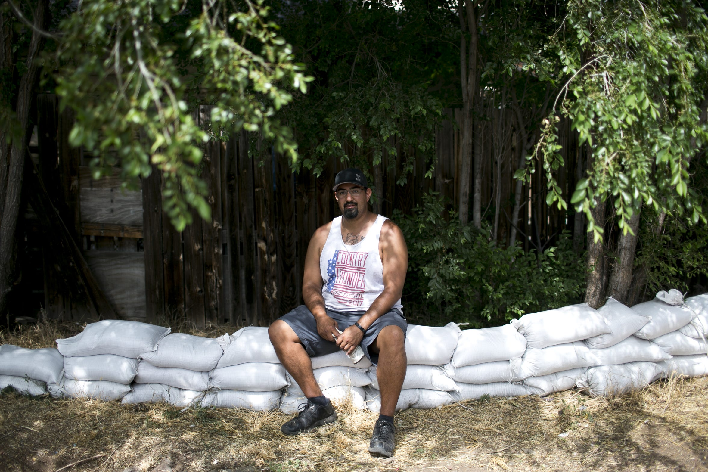 Flagstaff resident Richard Duran sits on a wall of sand bags he filled to protect his goddaughter's home from flooding in Sunnyside in Flagstaff on July 24, 2019. As the Museum Fire burned on in the mountains northwest of Flagstaff, residents in the Sunnyside community prepared for flooding feared to be worsened in the monsoon season due to the fire.