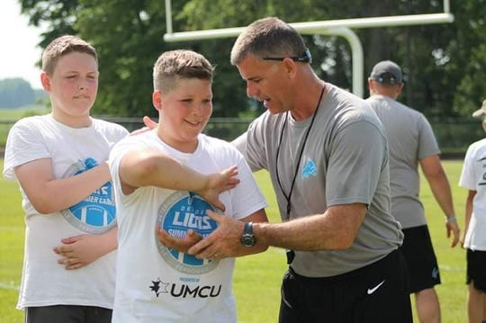Former St. Clair High School football coach Bill Nesbitt teaches a technique during a Detroit Lions football camp this summer.