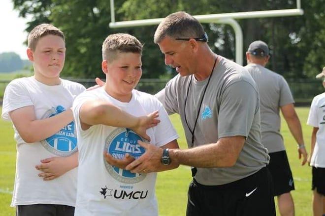 Former St. Clair High School football coach Bill Nesbitt teaches a technique during a Detroit Lions football camp this summer.