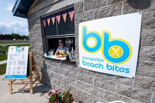Carlie Carter waits in the service window at Beach Bites Tuesday, July 23, 2019, at Chrysler Beach in Marysville. Beach Bites has opened in the concessions stand at the beach, and will remain open until Labor Day.