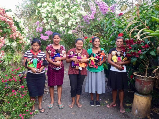 A collective of doll makers who are gardeners in Corozo, Nicaragua hold examples of their work.