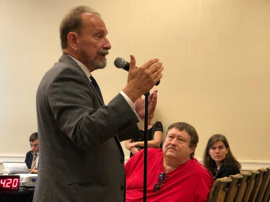 Activist Gene Stilp (left) speaks at a Three Mile Island decommissioning hearing as Scott Portzline, of anti-nuclear watchdog group TMI-Alert (middle) and Kim Conway, TMI-2 project manager (right) listen.   The public meeting was held Tuesday, July 23, 2019. The Unit 1 reactor will shutdown September 30.