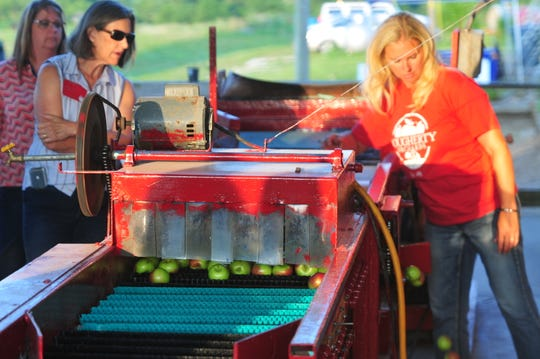 Owner Andra Solis demonstrates the grader during the Tuesday, July 23, 2019, Farm Tour at Dougherty Orchards.