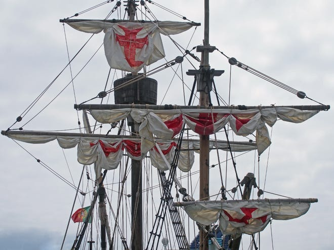 The masts sails and rigging of the santa maria a historic sailing ship in funchal harbour with white sails with red crosses