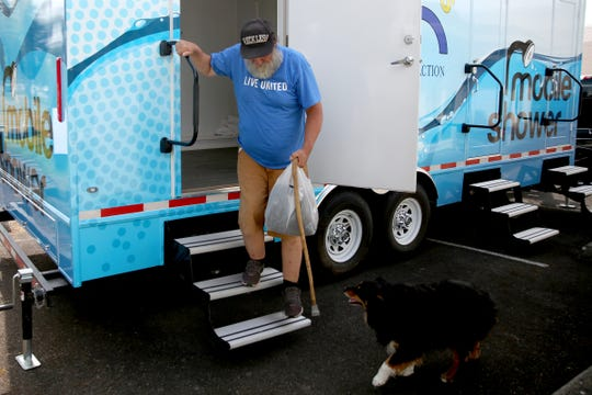 Ray Boyd is greeted by his dog Daisy as he exits a new trailer with three private showers that will soon be making its way around the area as a service for people experiencing homelessness. He lives in his car with his dog, Daisy, an Australian shepherd.