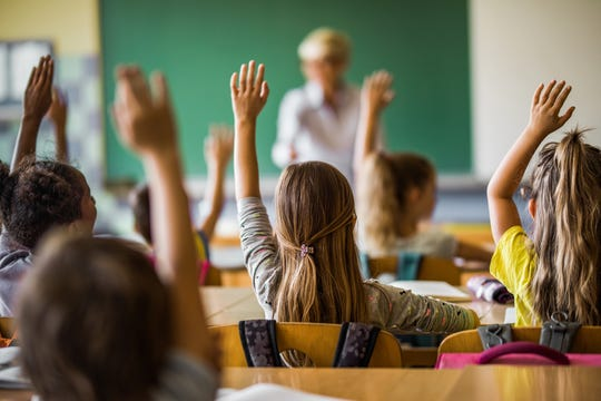 Students raise their hands in class.
